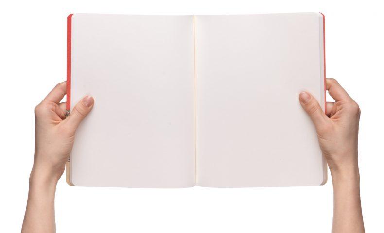 白紙のノートを読んでいる女性の手元