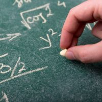 黒板に数式を書いている男性の手