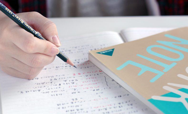 ノートを見ながら学習している学生
