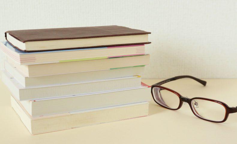 デスクの上に積み重なった本とメガネ