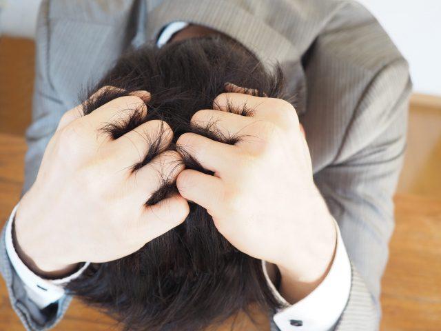 ストレスで頭を抱えている男性