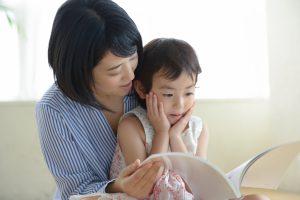 子供に本を読み聞かせるママ