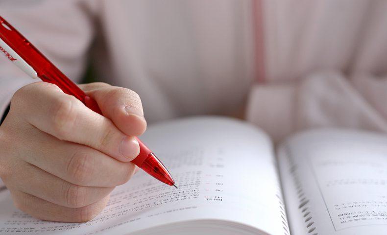 赤いペンで勉強している女性