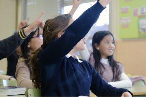授業中に手を挙げて質問する女の子