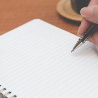 黒のペンでノートに書き込む