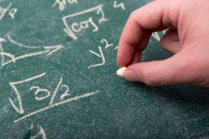 黒板に数式を書いている